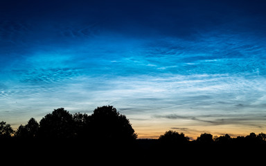 Rare Noctilucent clouds also known as silver clouds in the night sky in a rural scenery outside the city. These phenomenon clouds consist of ice crystals and are visible during astronomical twilight