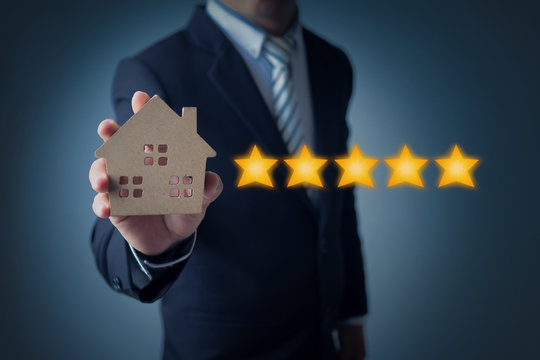 excellent service and best customer experience of real estate, business man showing 5 stars rating with wood home model on dark blue background