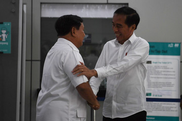 Indonesia's president Joko Widodo shakes hands with head of Gerindra party Prabowo Subianto as they arrive at a subway station during their meeting in Jakarta