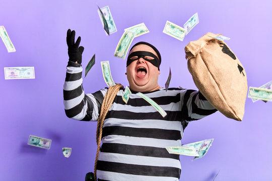 happy cheerful thief enjoying stolen money. isolated blue background studio shot. emotion and feeling