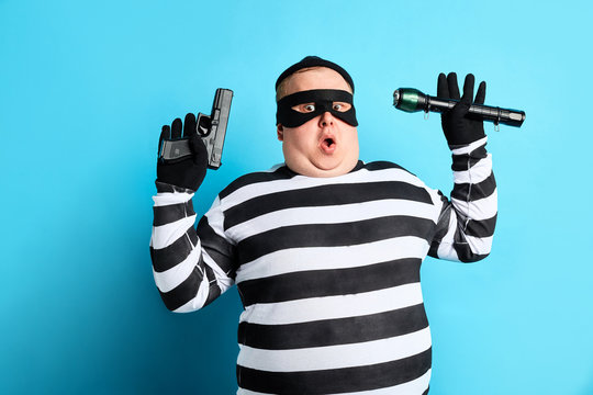 nervous unhappy burglar is being cought by police, isolated blue background. studio shot