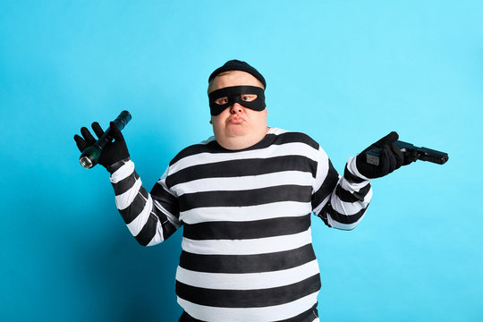 fat puzzled prisoner shrugging shoulders, he doesn't know how to destroy evidence. close up photo. isolated blue background. studio shot