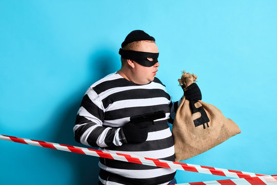 fat burglar in mask commiting a crime. close up side view photo. isolated blue background,studio shot.