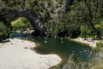 Top view of the Ardeche river near the famous Vallon Pont d'Arc arche with tourists kayaking, swimming et sun bathing. France.