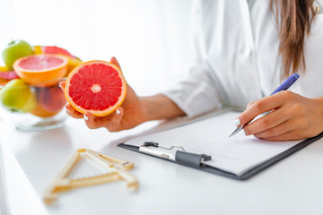 Doctor nutritionist writing case history in the office. Young woman dietitian prescribing recipe. Female nutritionist sitting at table with clipboard and healthy products on white background