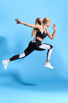 motivated woman runner on blue background. Dynamic movement. motivation. lifestyle, free time, spare time. studio shot. side view full length photo. cross fit