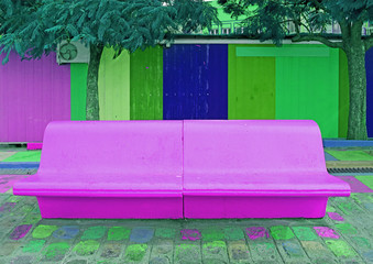 Pop art styled concrete bench in vibrant purple with green and blue wooden wall in the backdrop