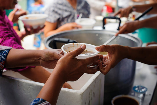 Concept of food sharing for the poor to alleviate hunger : Hands of beggars accepting food from the hands of volunteers who come to help free food breaks