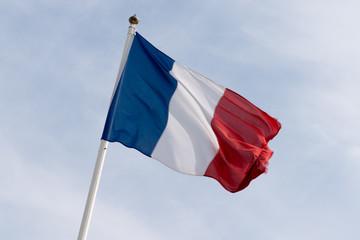 Flag of France waving over a cloud sky
