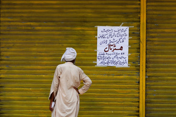 A worker reads a sign on a closed shop during a shutter down strike in Peshawar