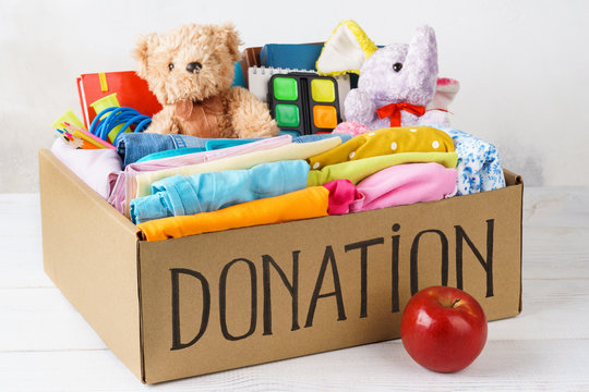 Different donations in a box - clothes, stationery and toys.