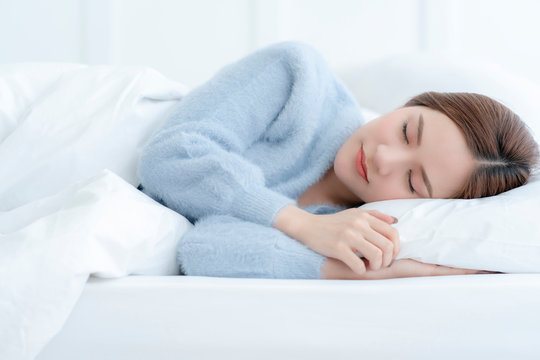 beautiful asian woman casual dress sleep well on white bed daylight morning time