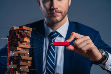 business man try to build wood block on wooden table and black background business organization...
