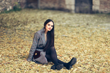 Beautiful girl wearing winter coat sitting on the floor of an urban park full of autumn leaves.