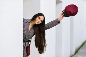 Young beautiful girl with very long hair wearing winter coat and cap outdoors