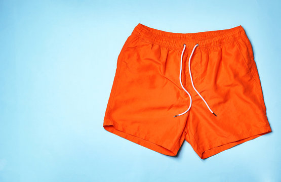 Stylish male swim trunks on color background, top view with space for text. Beach object