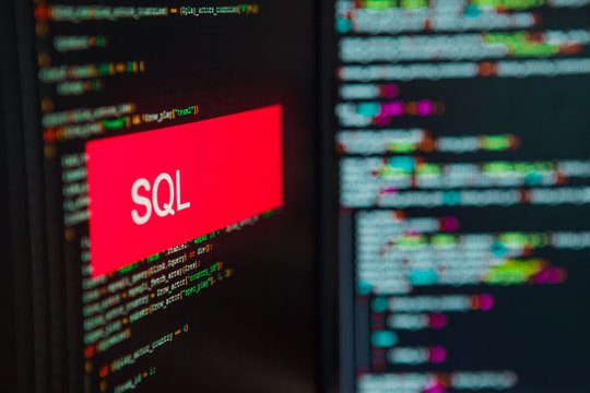 Programming language, SQL inscription on the background of computer code.