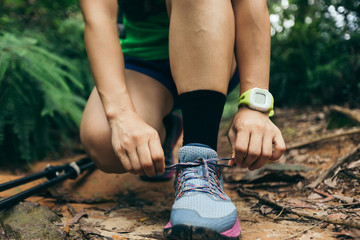 Woman ultra marathon runner tying shoelace on forest trail
