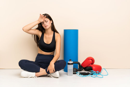 Teenager sport girl sitting on the floor with tired and sick expression