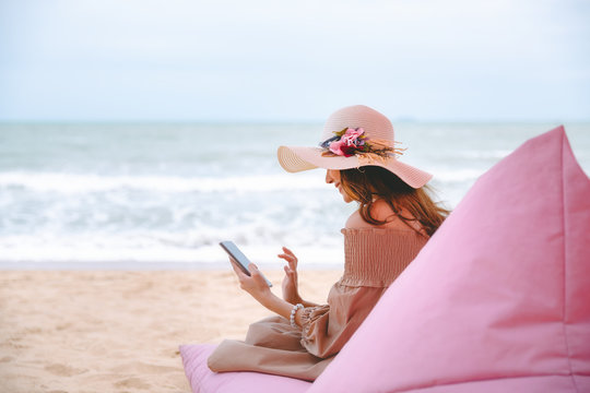 Woman with mobile phone in cafe on beach