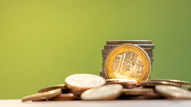 Concept of investment and saving money. Pile of euro coins on wooden table.