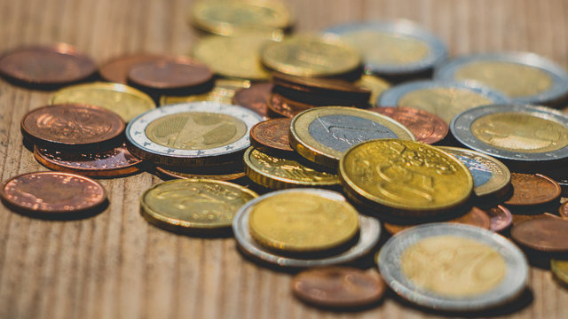 Euro coins on wooden texture