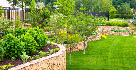Deurstickers Pistache Landscaping in home garden. Beautiful natural landscape design with flower beds in summer. Panoramic view of landscaped part with plants in yard or backyard of residential house.