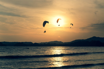 Beautiful Silhouette of paraglider flying in the sky of sunset on the beach. Wall mural