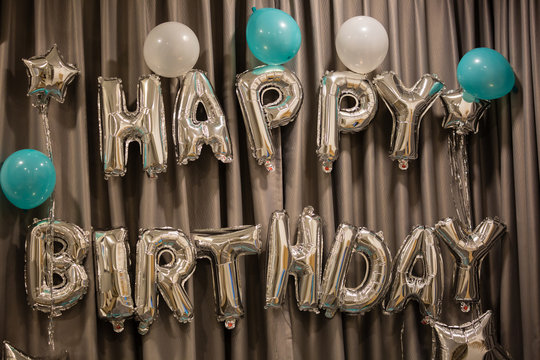 Upper case letters HAPPY BIRTHDAY from silver balloons view