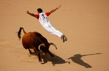 A recortador jumps over a bull during a contest in a bullring at the San Fermin festival in Pamplona