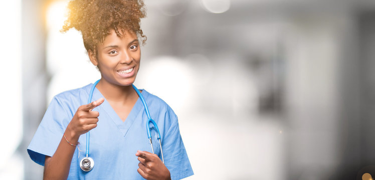 Young african american doctor woman over isolated background pointing fingers to camera with happy and funny face. Good energy and vibes.
