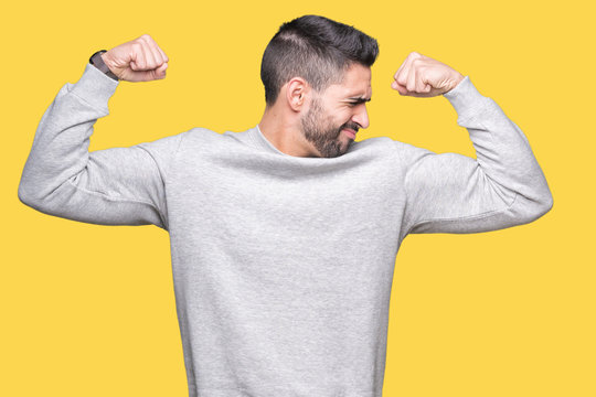 Young handsome man wearing sweatshirt over isolated background showing arms muscles smiling proud. Fitness concept.