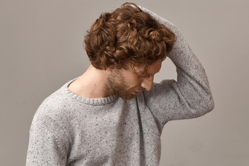 Handsome fashionable unshaven bearded young Caucasian male with wavy hairstyle dressed in trendy gray knitted pullover, looking down and touching his reddish hair, having deep in thoughts look