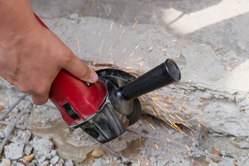Close up hand and electric wheel with sparks from the grinding wheel