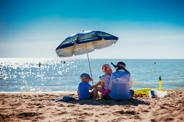 mother with children sit under an umbrella on the seashore on a hot day