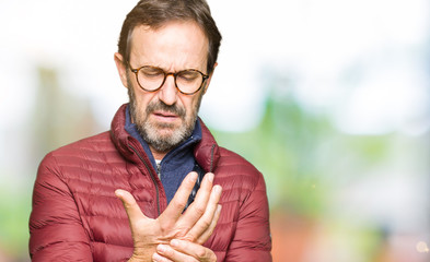 Middle age handsome man wearing glasses and winter coat Suffering pain on hands and fingers, arthritis inflammation