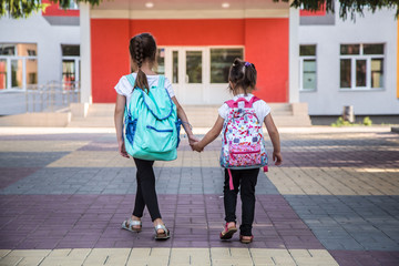 Back to school education concept with girl kids, elementary students, carrying backpacks going to...