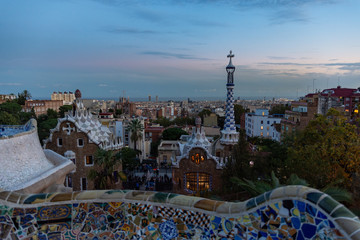 Foto op Canvas Barcelona View of Barcelona from Park Guell at the sunset. In the foreground the colourful buildings of the main entrance. Barcelona.