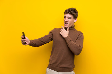 Handsome young man over isolated yellow background making a selfie