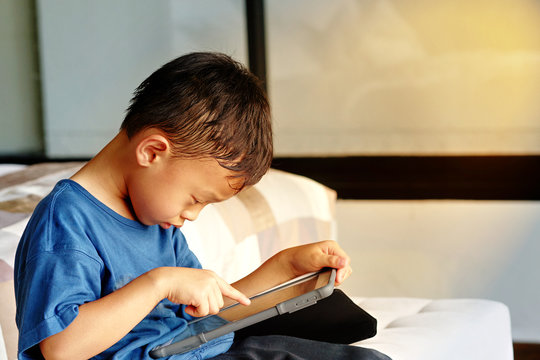 Boy play smart phone tablet in concentration alone in room in family care and ADHD concept