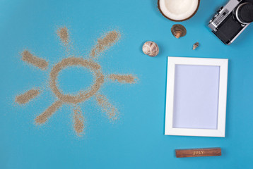 Photo frame and camera on blue background. Sun drawn by the sand on blue background. Top view.