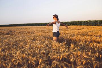 Beautiful Young Woman Outdoors Enjoying Nature in Wheat Field