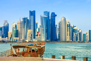 Traditional wooden dhow on foreground at Doha Bay and skyscrapers towers of West Bay skyline on background. Capital of Qatar, Middle East, Persian Gulf. Sunny blue sky. Urban modern cityscape. Fototapete