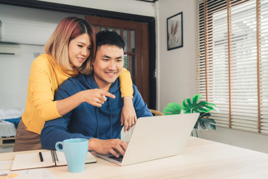 Young asian couple managing finances, reviewing their bank accounts using laptop computer and calculator at modern home. Woman and man doing paperwork together, paying taxes online on notebook pc.