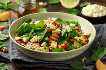 Summer Peach Salad with spinach, avocado, walnuts and feta cheese in rustic bowl. healthy food.