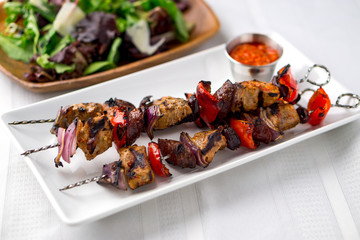 Pork kebabs skewers with sauce and salad. These delicious pork meat souvlaki were roasted on the bbq until well-grilled. Cooking food on skewers has been common in many cuisines since ancient times.