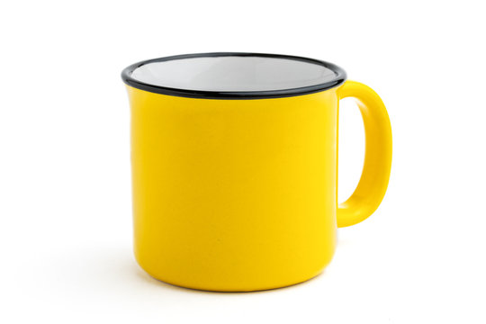 Side view of empty yellow enamel coffee mug isolated on white background.