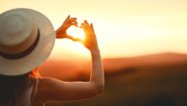 Happy woman with palms of your fingers in shape of a heart on sunset in nature  .