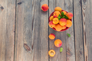 Ripe apricots in a bowl on wooden rustic background copy space