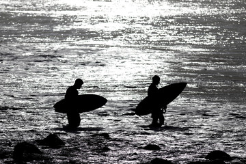 Two surfers get in the water at Punta Roca Beach in La Libertad